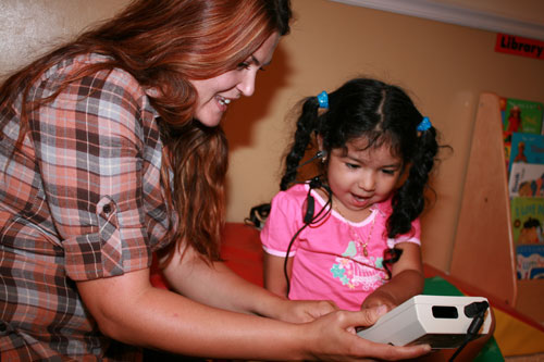 a woman showing an hearing screening device to a smiling girl